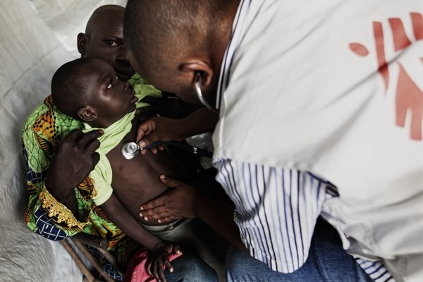A young patient is seen by an MSF staff during a mobile clinic.