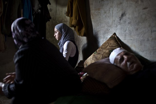 An elderly Syrian refugee suffering from Parkinson's disease sleeps in a room in a ramshackle home surrounded by his daughter-in-law and granddaughter