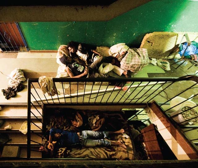 Zimbabweans sleep in the shadows of a stairwell in the Central Methodist Church in downtown Johannesburg. The Church provides a 'safe haven' where thousands of Zimbabweans seek refuge every night.