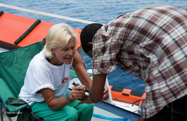 After a rescue by MOAS, nurse Mary Jo assesses people's health situation on the main deck of MY Phoenix.