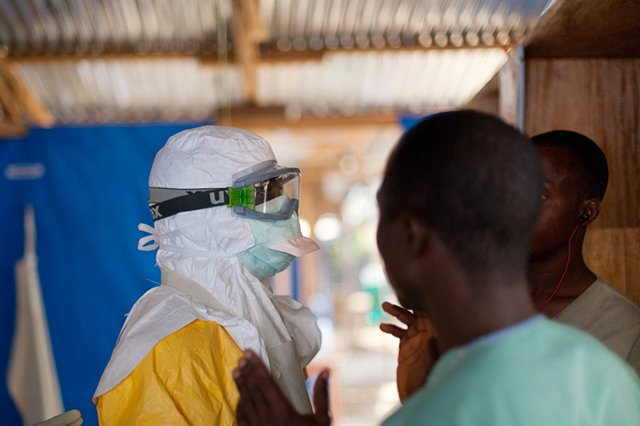 A MSF psychosocial counsellor dresses up in full protective gear before talking to patients in the high risk zone at the MSF Ebola Treatment Center in Guéckédou, Guinea. Photo: Peter Casaer