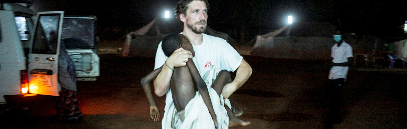 MSF Doctor Clement Van Galen carries a child with meningitis in critical condition. Photo: Sylvain Cherkaoui/Cosmos