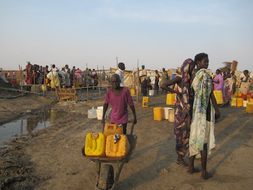 """People collecting water in the """"Protection of Civilians"""" site near Bentiu. Photo: Beatrice Debut"""