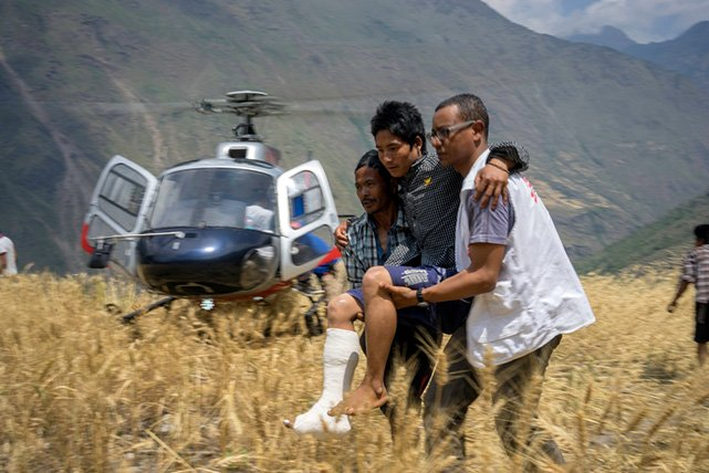 Maila Gurung, 26, is helped to get off a helicopter when he returned home to Diol village, Gorkha District, Nepal, on May 21 2015. Maila had been evacuated to the MSF inflatable hospital in Arughat Bazaar where his broken leg was treated. Photo: Brian Sokol/Panos
