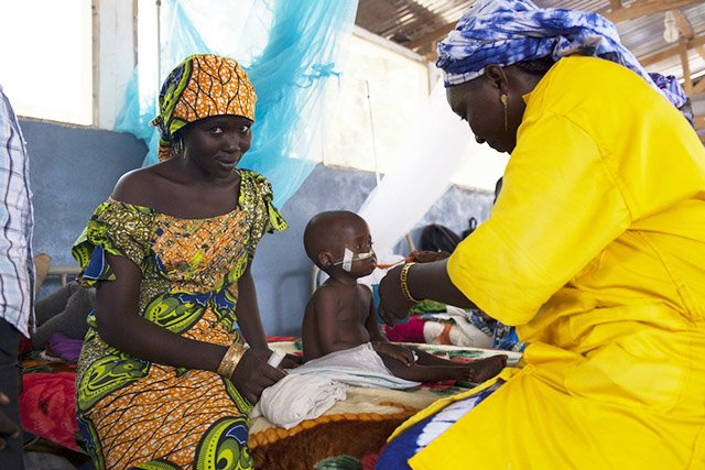A hospitalised malnourished child is being fed by a nurse in the intensive therapeutic feeding centre MSF set up next to the Mokolo Hospital. Photo: Tristan Pfund