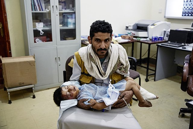 "A father holds his wounded child at the MSF supported Ministry of Health hospital in Sa'ada city. Saudi led coalition forces have been carrying out air strikes on a daily basis in Yemen's Sa'ada warning civilians to leave the province after declaring the entire territory a ""military target"". June 15, 2015. Photo: Sebastiano Tomada/Getty Reportage"