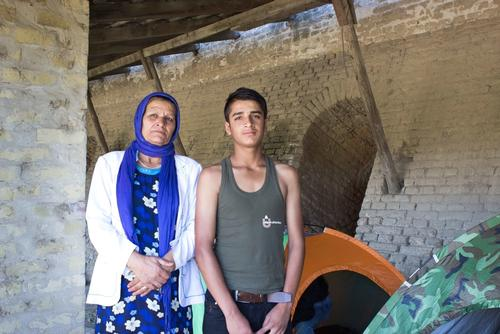 Haseeb, 13, and his mother Zubida stand amongst refugees' abandoned tents in the old brick factory in Subotica, Serbia. Photo: Ilija Gudnitz Weber/MSF