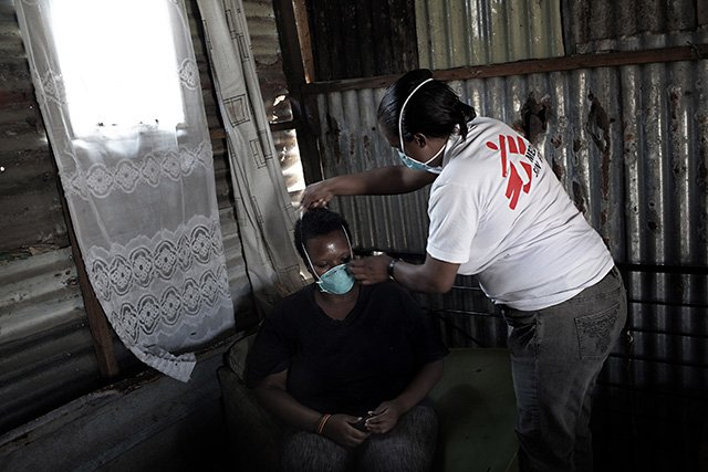 XDR-TB survivor and peer counselor, Xoliswa Hermanus, helps a family member fit a mask to prevent TB infection during a home visit and group counseling session. Photo: Jose Cendon