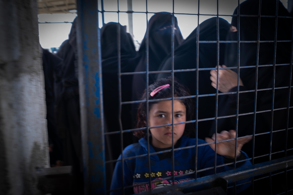 A young girl looking through a closed fence in Al-Hol Camp, Eastern Al- Hasakah Governorate, Northeastern Syria.