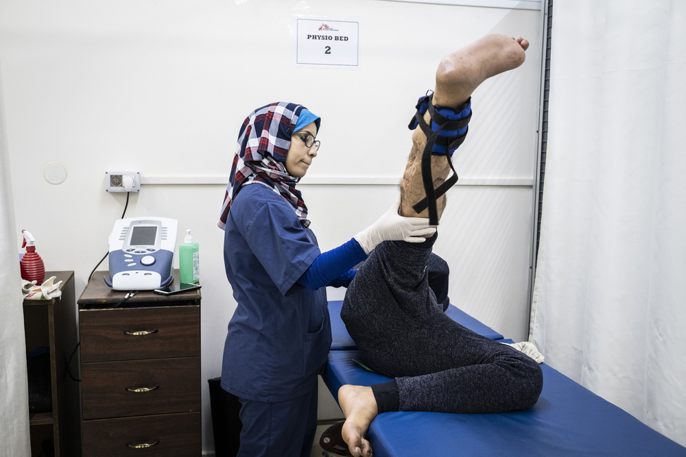 Sabrine Wadi, a physiotherapist working with MSF at Al Awda hospital in northern Gaza, assists a patient with his physiotherapy exercises.