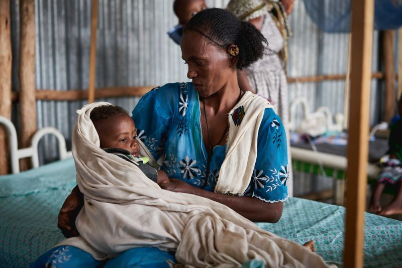 Mother holds baby - affected by Malaria
