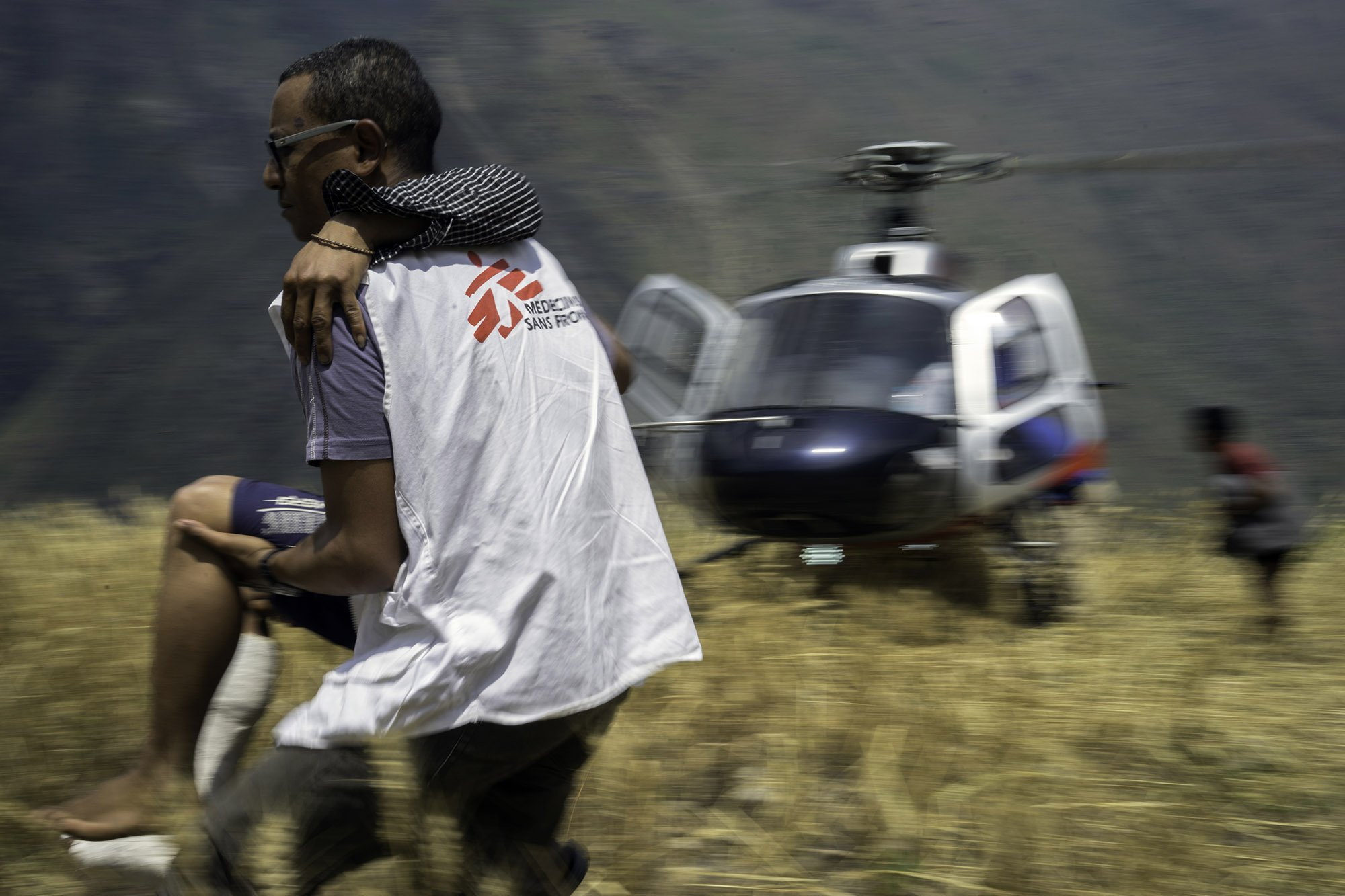 Maila Gurung, 26, is assisted off of a helicopter by MSF Dr. Hanni. Photo: Brian Sokol