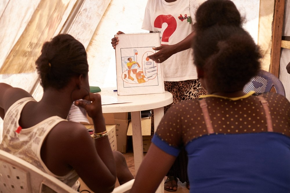 An HIV activist undertakes an awareness session on HIV transmission at the MSF mobile clinic in the neighbourhood of Sangoyah Market. Copyright: Sam Phelps