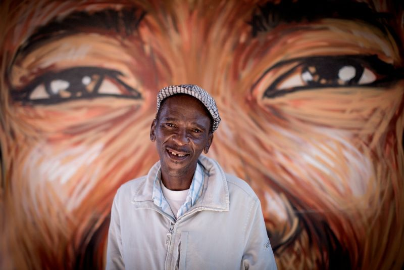 Simphiwe in front of a community mural at his local clinic in Kuyasa, Khayelitsha