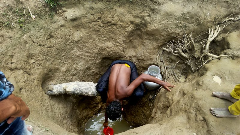 Bangladesh, Watson, Clean Water: A man scoops water from a hand-dug well in Unchiparang makeshift settlement, home to 33,000 of the half a million Rohingya refugees who have fled violence in Myanmar since the end of August 2017