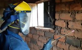 A sprayer is treating a house against mosquitoes during the 2019 indoor residual spraying campaign in Kinyinya health district.