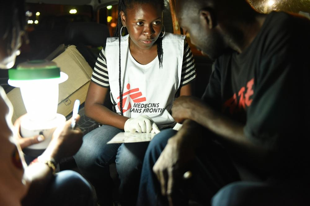 Councelor Celina Beatriz Chinhaja conducts an HIV pre-test and counseling with a truck driver inside the MSF car at a remote parking area outside Beira City, Mozambique