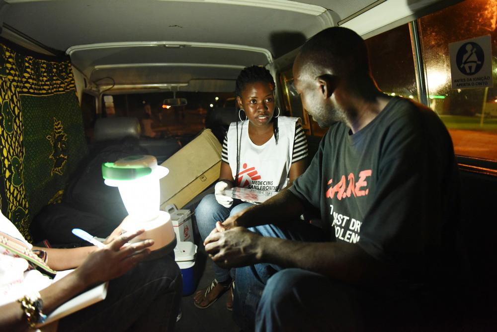 Councelor Celina Beatriz Chinhaja conducts an HIV pre-test and counseling with a truck driver inside the MSF car at a remote parking area outside Beira City, in Mozambique