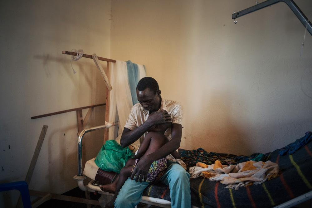 Joseph holds his two-year-old daughter, Bhileru, who is suffering from measles, in the health facility run by MSF